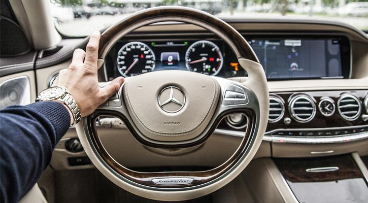 a man's hand on the steering wheel of a car