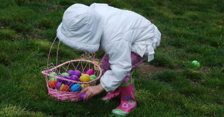 a little girl in a white coat and Easter basket bending over to pick up eggs