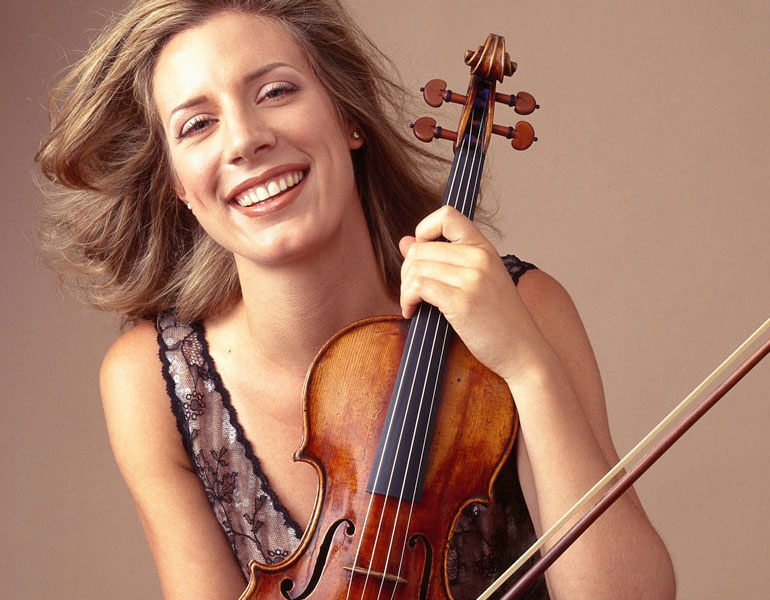 a woman holding a violin and smiling