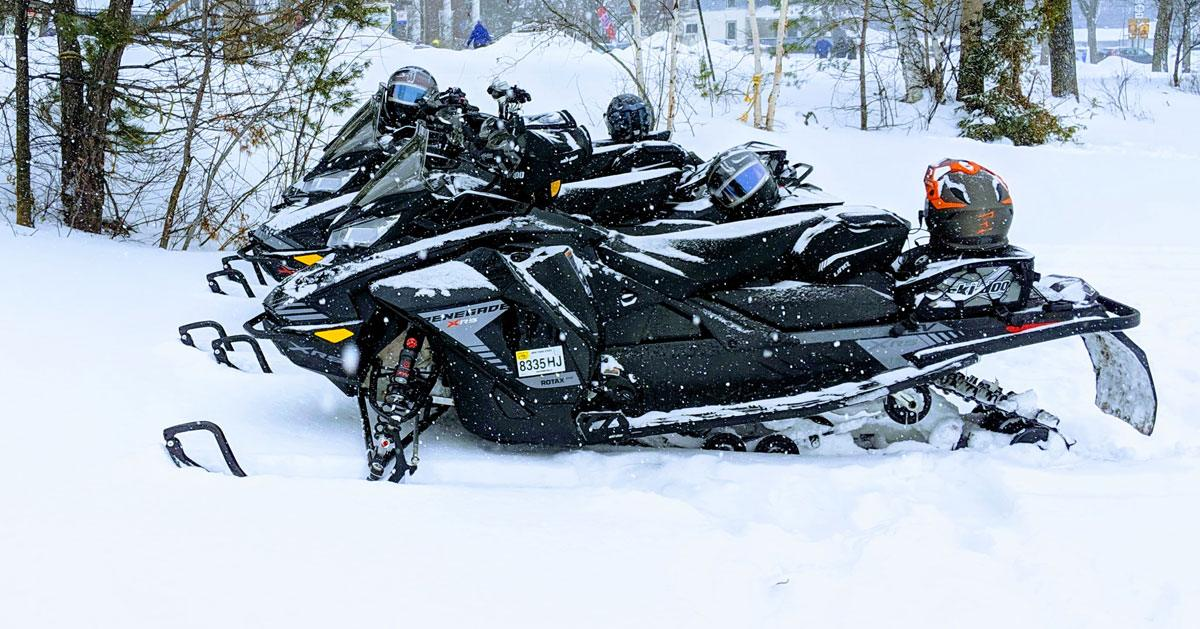 a group of snowmobiles parked on snow