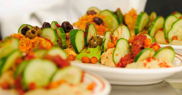 a beautiful salad with cucumbers, olives, and what looks like chickpeas and hummus
