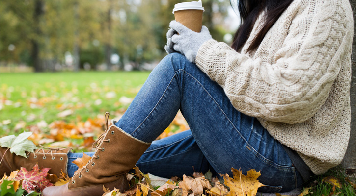 woman sitting against a tree, fall leaves around her, she's holding a coffee, her head is cut off from view