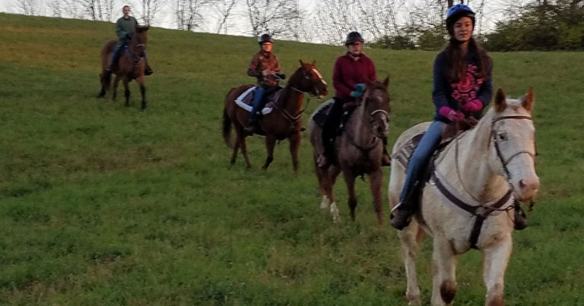 group of people riding horses