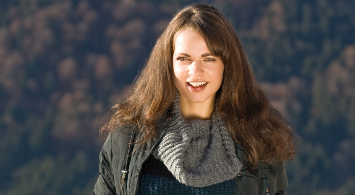 a brunnette women with a grayish sweater, jacket, and scarf on