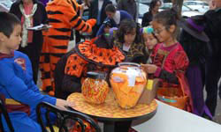 kids in costumes looking at a giant jar of candy corn