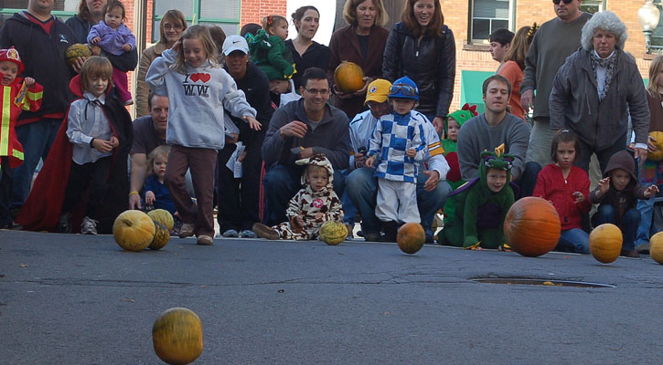 crowd watches as kids roll pumpkins in a race