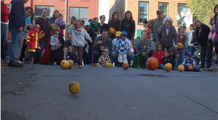 crowd of people watching kids roll pumpkins