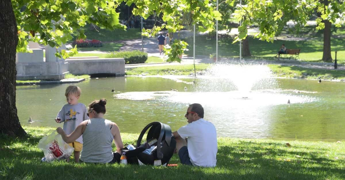 a family having a picnic by a pond in congress park