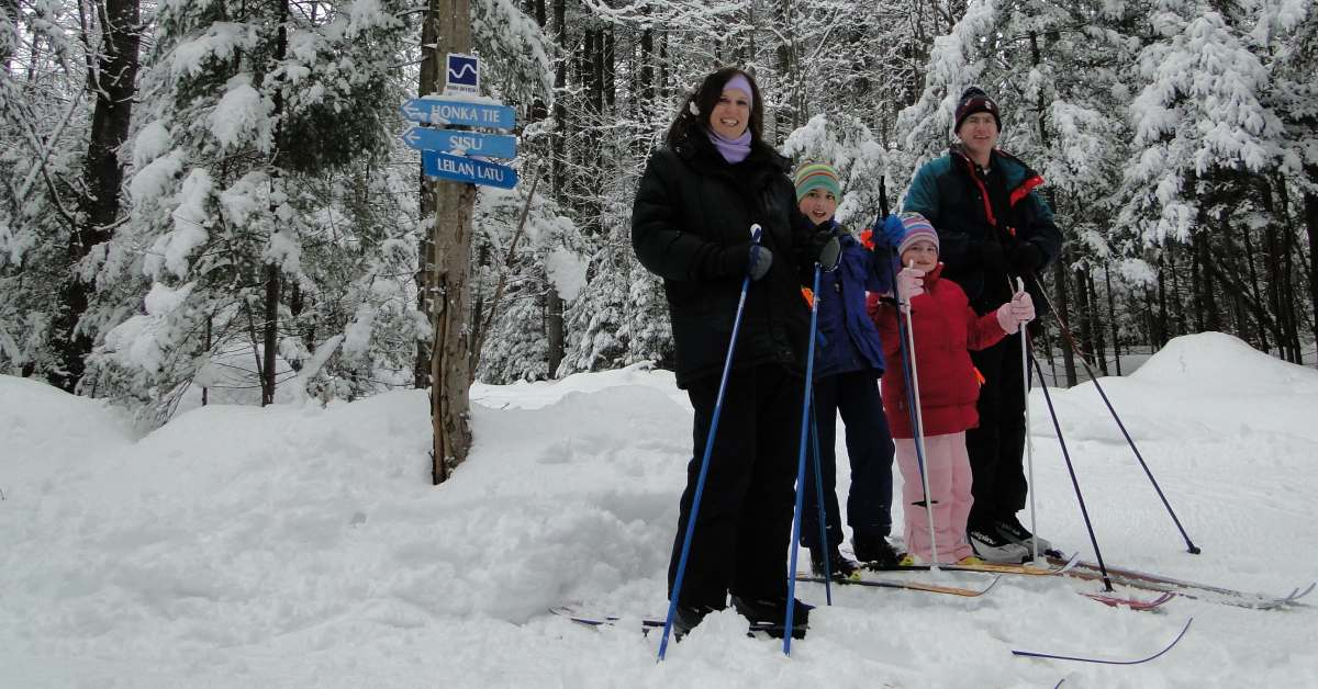 two adults and two kids wearing cross country skis on snowy ground