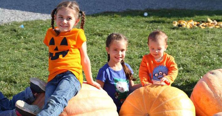 kids sitting on and behind pumpkins