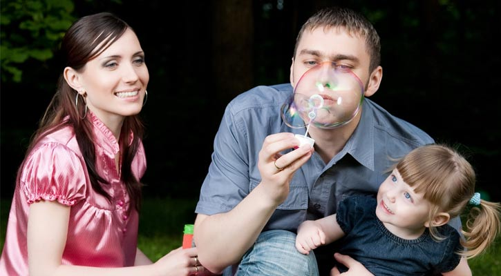 parents and their daughter posing in a park, the dad is blowing bubbles