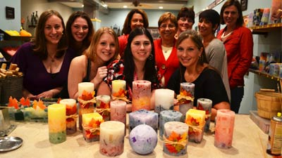 group of women standing behind homemade candles