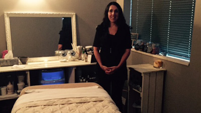 a female masseuse standing in front of a massage table