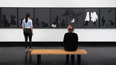 two women looking at art in a gallery
