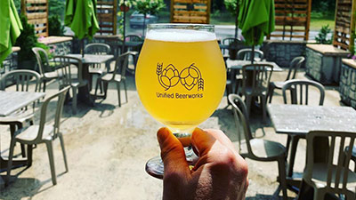 person holding a beer from unified beerworks