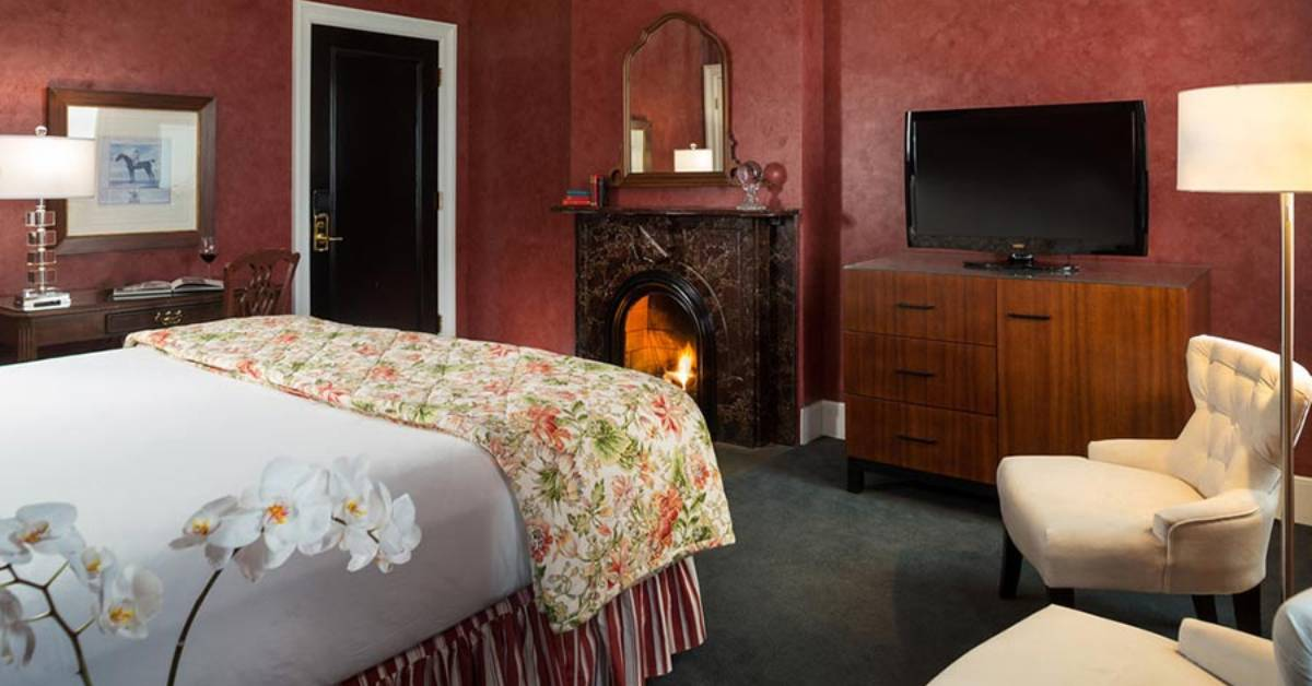 a fireplace near the foot of a bed in a hotel guest room