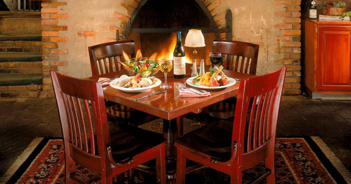 table with food in front of a fireplace