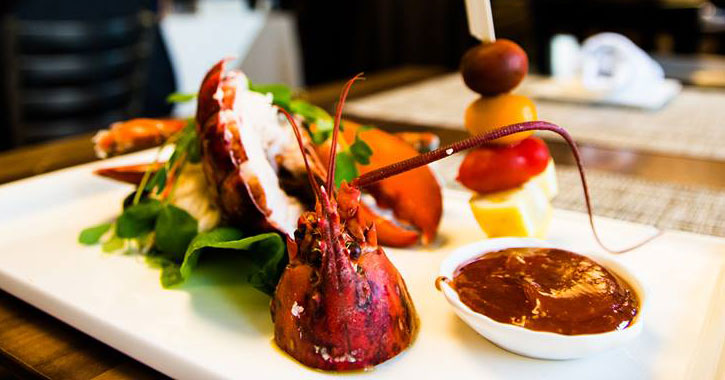 an elegant plate of seafood including a lobster head