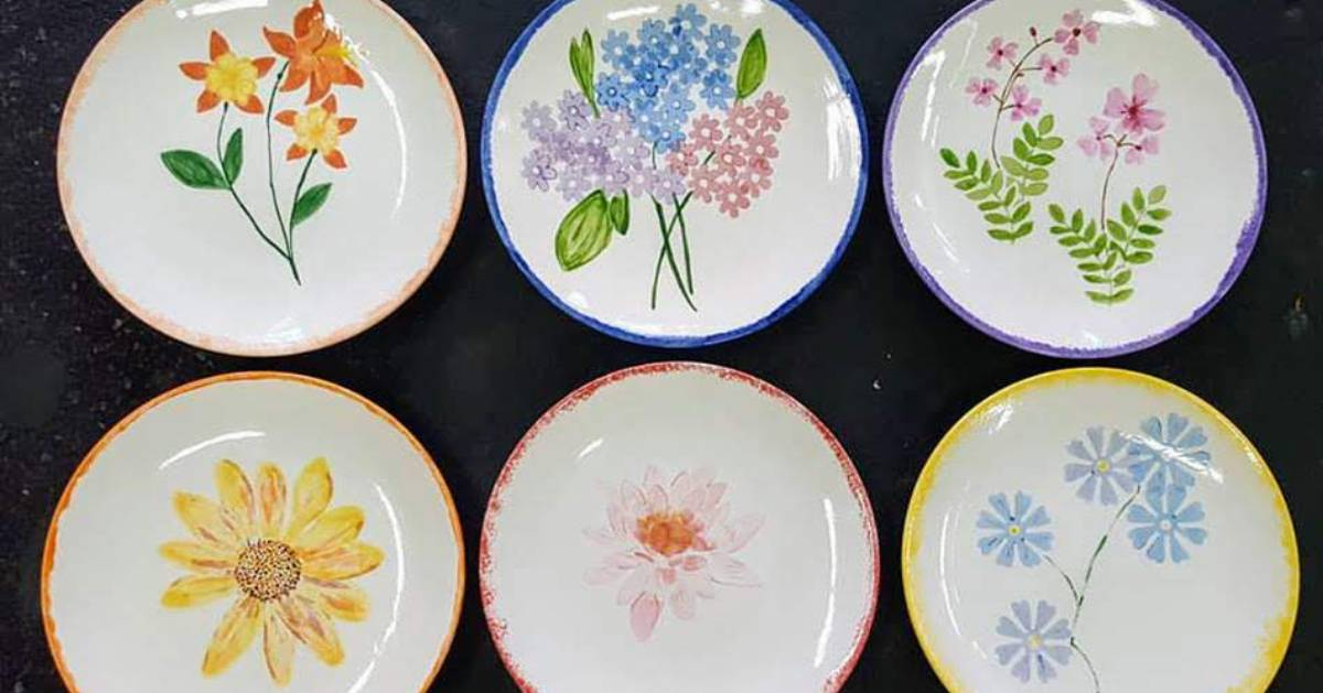 six plates with handpainted flowers on them
