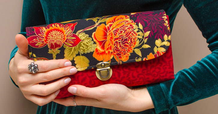 close up of a woman holding a clutch with a floral pattern