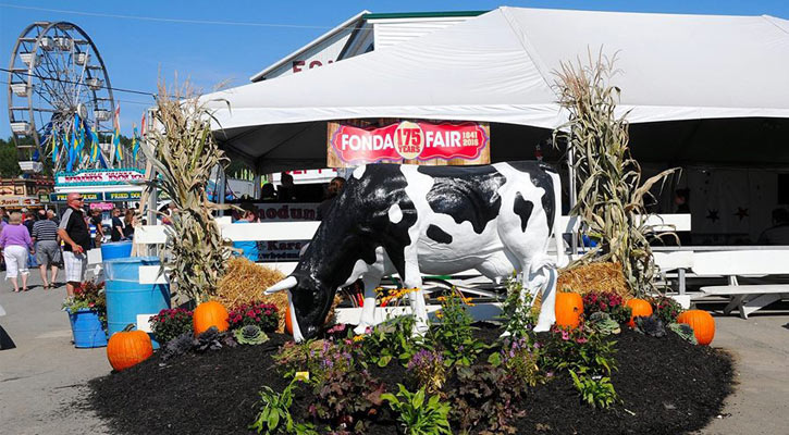 cow display in front of fair tent, ferris wheel in background