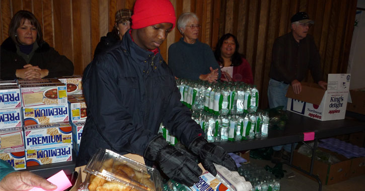 a man putting together food for a food drive
