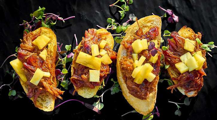 four fancy pieces of bread with what looks like a pulled pork and pineapple mixture on each