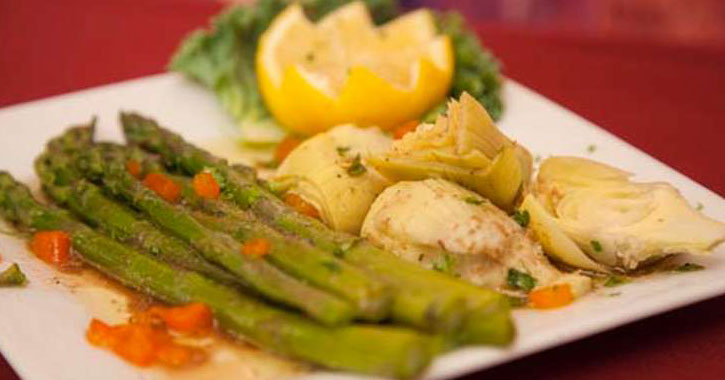 asparagus and artichoke hearts on a square white plate with a uniquely cut lemon
