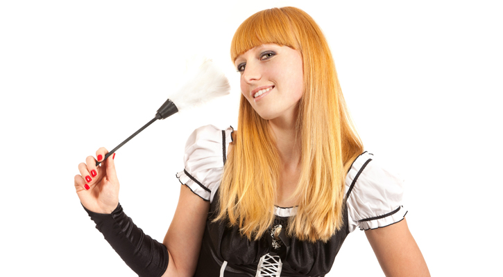 a redheaded woman in a French maid costume tilting her head, smiling, holding up a feather duster