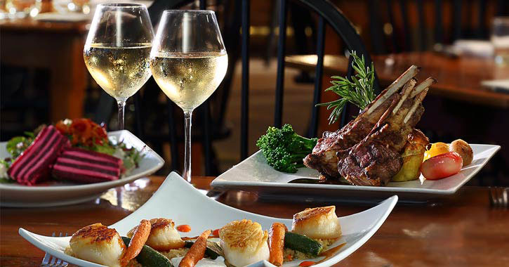 elegant place setting with two glasses of white wine and plates of scallops and what looks like lamb chops