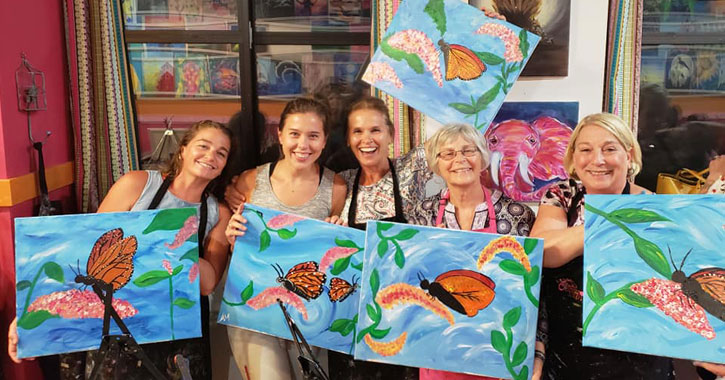 several women holding up their paint and sip paintings