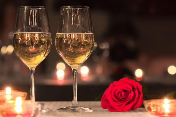 two glasses of wine and a rose