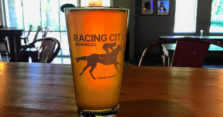 a Racing City Brewing glass of beer on a bar