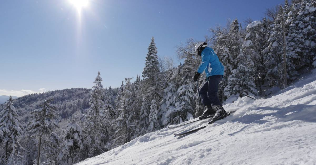 skier wearing blue coat going down a hill
