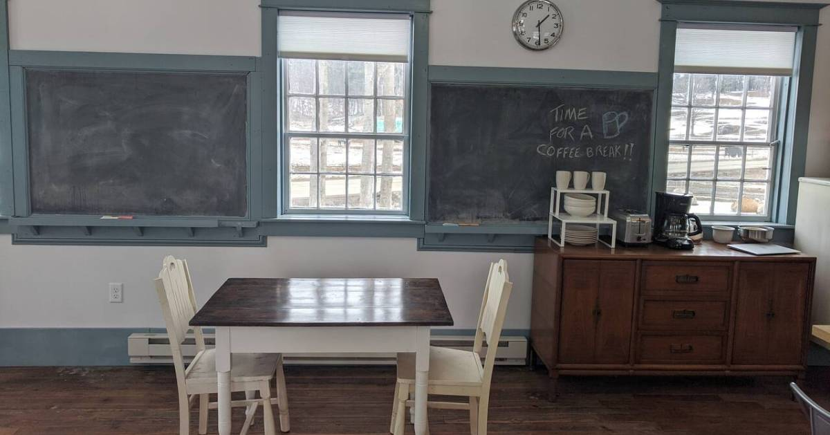 schoolhouse room with a table and chalkboards and windows