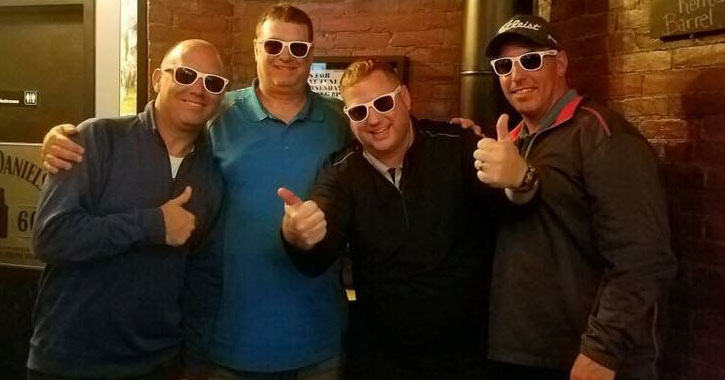 four guys in sunglasses posing together