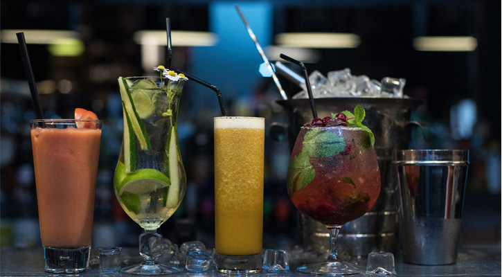 four cocktails in a row on a bar