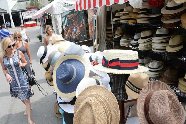 people walking by a vendor selling hats