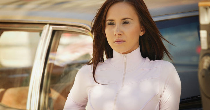 a woman leaning against a car with a white sweater zipped up high