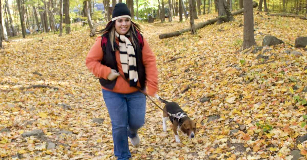 a woman hiking in the woods with a beagle