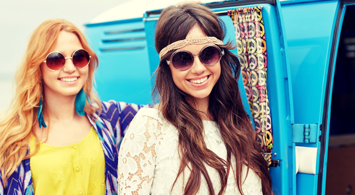 two women dressed as hippies standing by a lightblue/baby blue van
