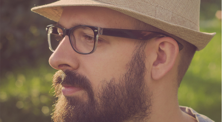 close up of a man's face - he has a beard, glasses, and is wearing a fedora-like hat