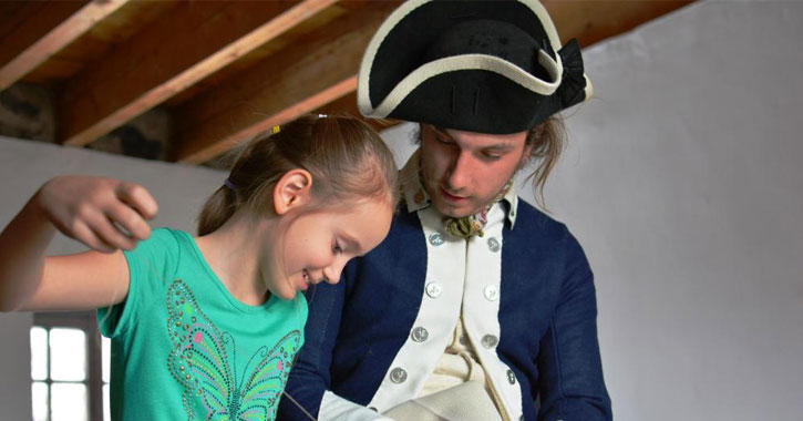 a man dressed in Colonial attire is showing a little girl what looks like how to sew