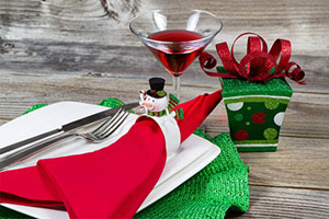 a red and green place setting with a cocktail and small present