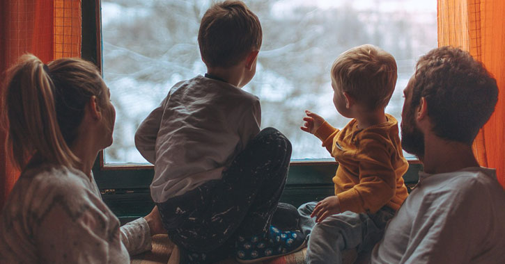 a family looking out a train window at snow