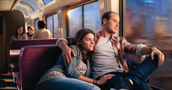 a couple on a train looking happily out the window