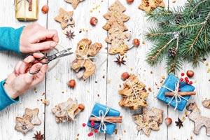 hands cutting ribbons around homemmade ornaments and cookies