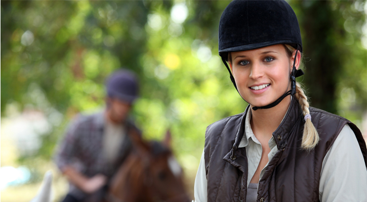 a woman in a horse back riding outfit, another horseback rider in the background