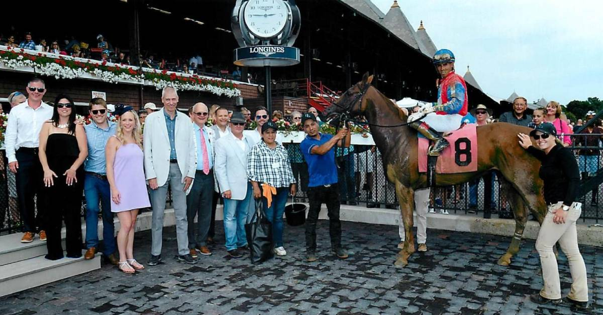 people standing in winners circle with horse and jockey