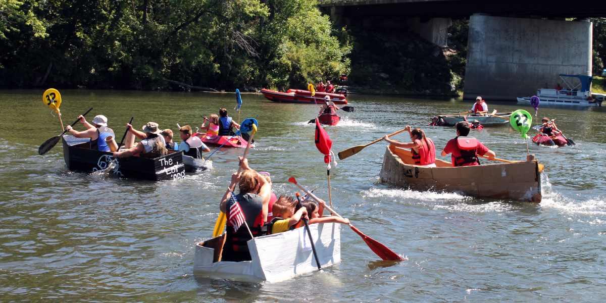 competitors racing cardboard boats at hudson crossing